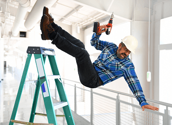 Man wearing a plaid shirt and a hard hat holding an electric drill falling off of a ladder